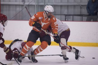 A UT skater get's tangled up with Texas State players in Friday's game.