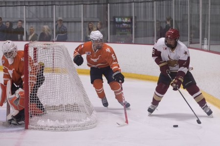 Texas State's Tyler Colbert skates behind the net Friday night, while UT's David Hutto, in goal, watches for the puck.
